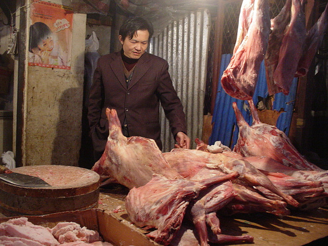 Un boucher devant des carcasses de chiens à Wuhan, Chine. (photo flickr/andydoro)