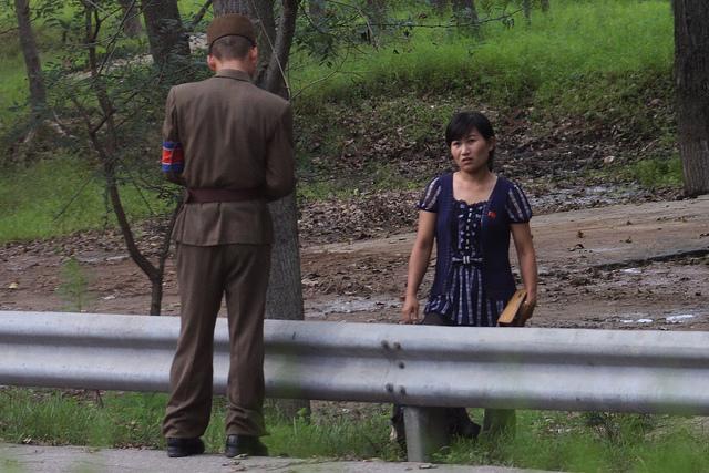 Une femme est contrôlée à l'un des nombreux checkpoints présents en Corée du Nord. (photo flickr/roman-harak)