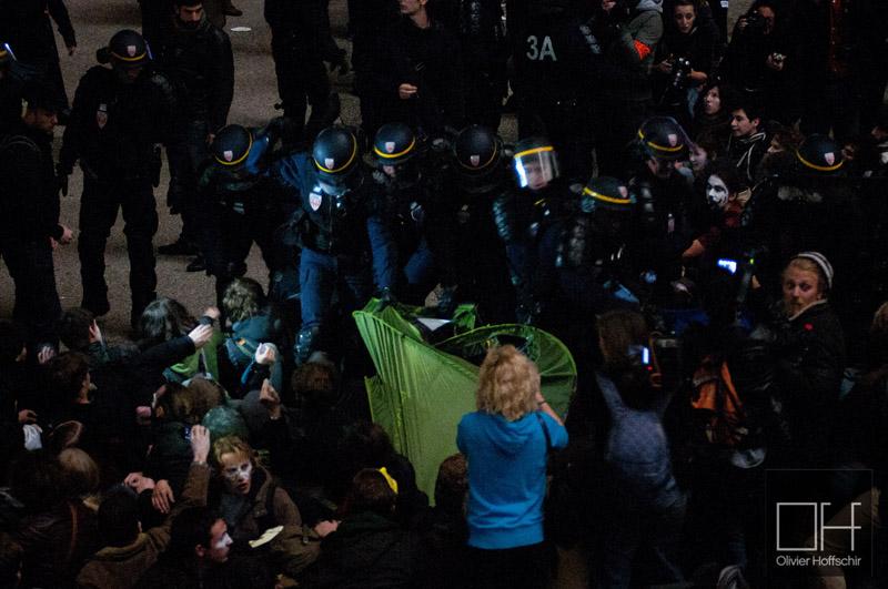 """Évacuation du campement """"Occupy la Défense"""" quelques heures après son installation. Les CRS chargent le campement pour confisquer les tentes, s'en suit des scènes ubuesques ou des groupes de manifestants font du """"tiré à la corde"""" avec un régiment de CRS, avec une tente en guise de corde. (photoOlivierHoffshir/8e étage)"""