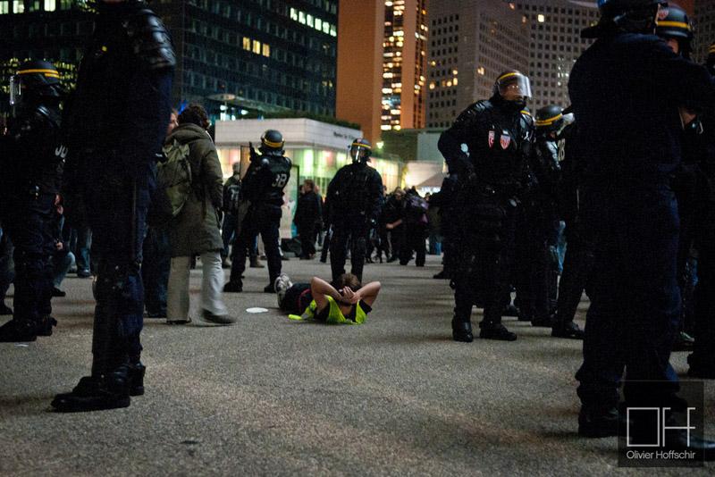 """Un manifestant de Occupy la Défense se repose au milieu des CRS après sont """"expulsion manu militari"""" du campement. (photoOlivierHoffshir/8e étage)"""