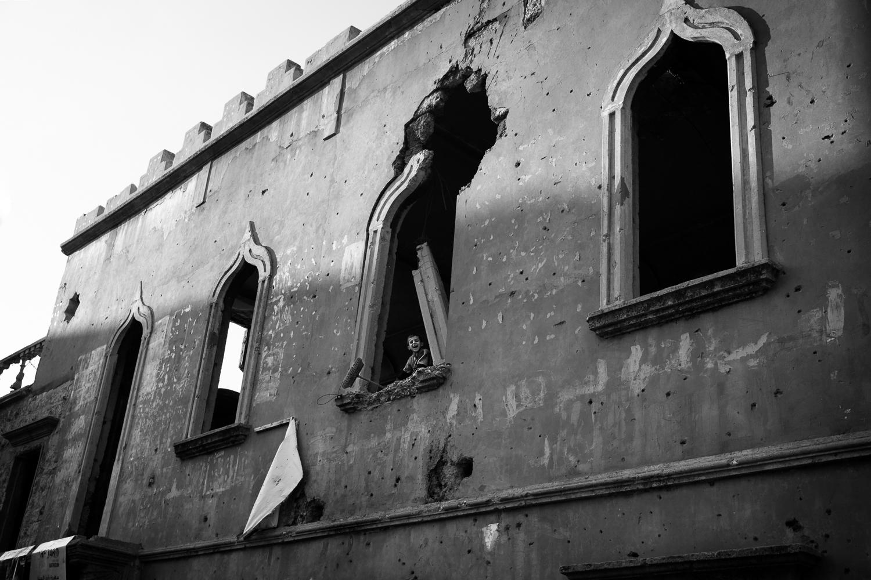 Un gamin regarde à travers la fenêtre d'une école éventrée par une bombe lâchée par Israel en 2006. (photo Baudouin Nach/8e étage)