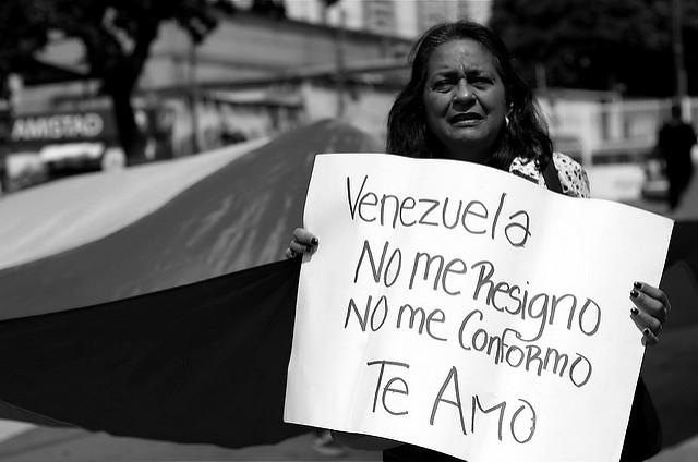 """Une manifestante brandit une pancarte avec l'inscription """"Je ne me résigne pas. Je ne me fait pas une raison. Je t'aime"""" en 2015. (Photo Flickr/Carlos Díaz)"""