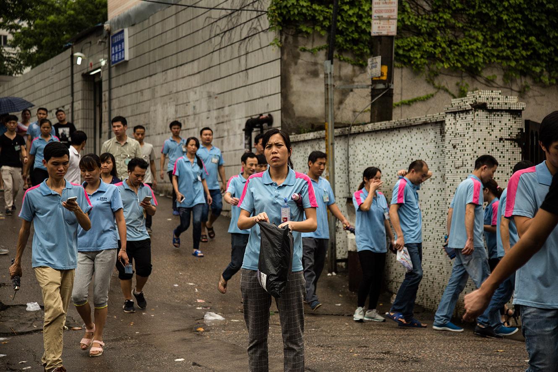 Des ouvriers d'une usine fabriquant des vitres de smartphone sortent de l'usine à 7 heures du matin, après avoir travaillé toute la nuit. (photo Julie Zaugg/8e étage)