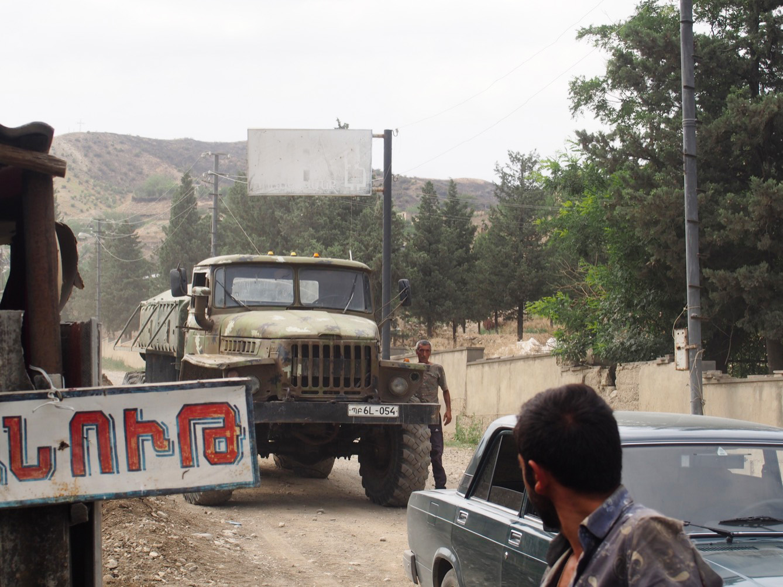 Un camion militaire venu ravitailler en eau les troupes karabakhtsis est accueilli par des évacués dans la ville de Talish, au nord-est du Haut-Karabakh. Derrière la colline (arrière-plan), se trouve la ligne de front et l'Azerbaïdjan. (photo Arthur Fouchère/8e étage)