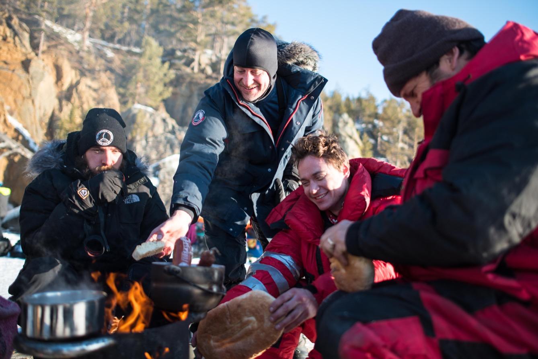 Tout le monde est rassemblé autour du feu pendant le dégel du pain de glace.