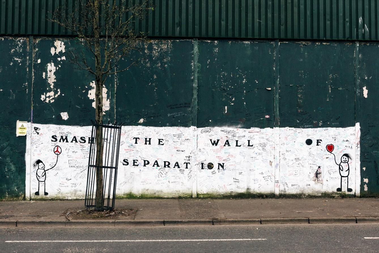 Peinture murale appelant à détruire les murs de séparation à Belfast. Sur l'applat blanc on peut lire de nombreux messages écrit par les gens de passage. (photo Yann Levy/8e étage)