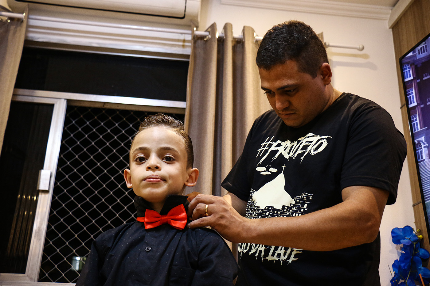 João termine de se préparer avec l'aide de son père.  (photo Collectif Singulier/8e étage)